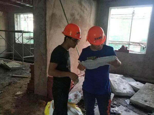 施工员正在查看图纸商量如何综合布线